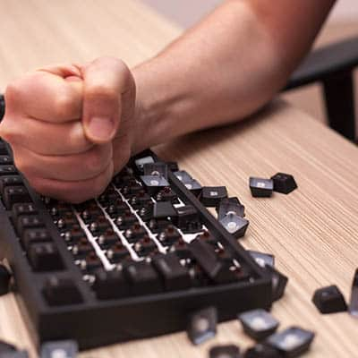 Clenched fist pounding on a computer keyboard