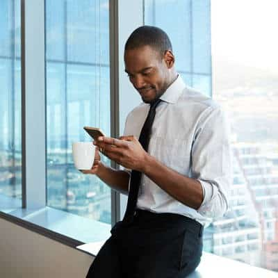 Employee holding coffee mug and looking at smartphone