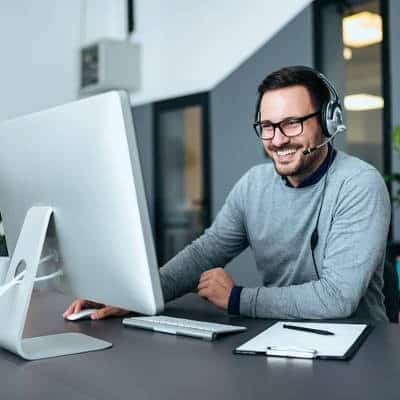 Employee smiling while looking at his computer