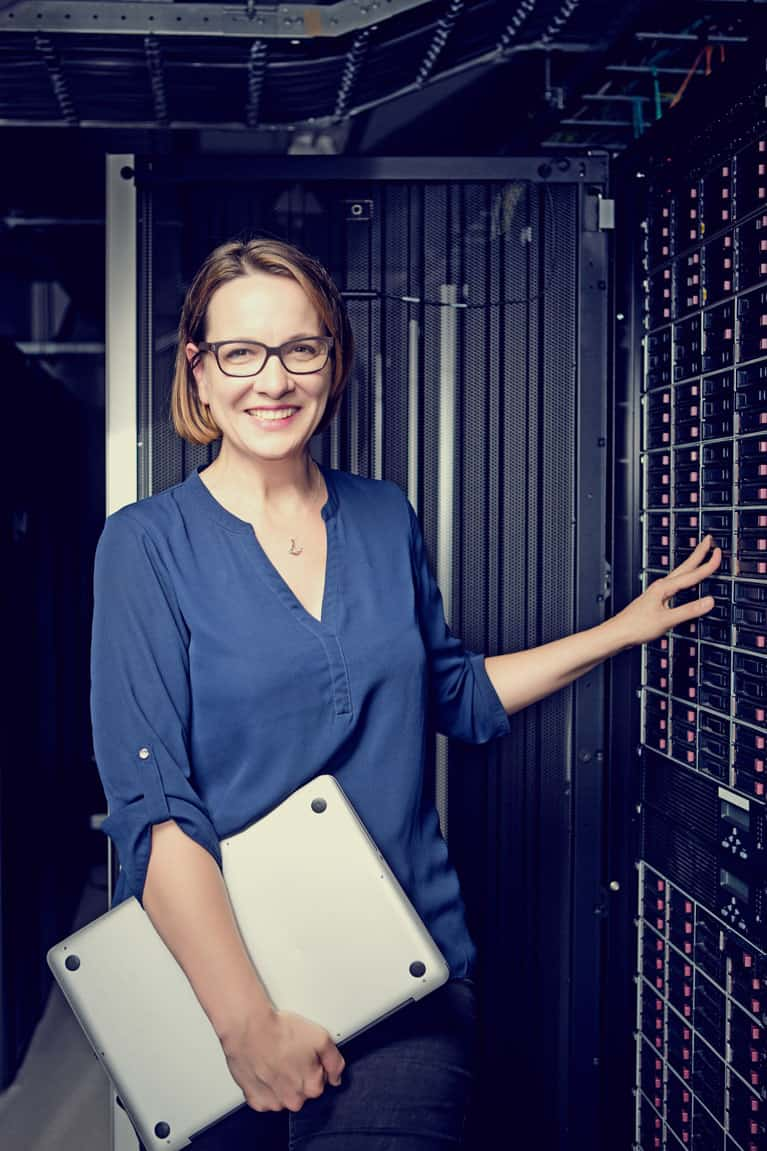 Businesswoman Holding Laptop in Server Room